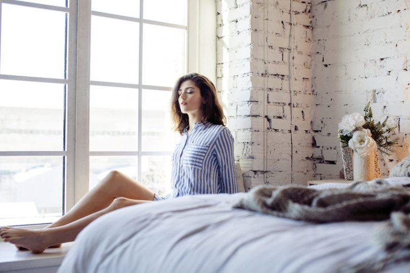Mulher sentada na cama.