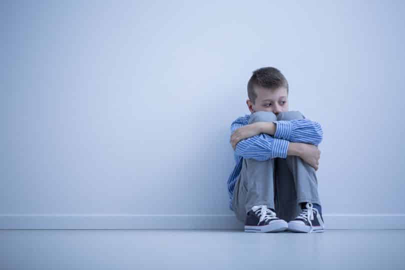 Menino sentado sozinho no chão contra a parede.