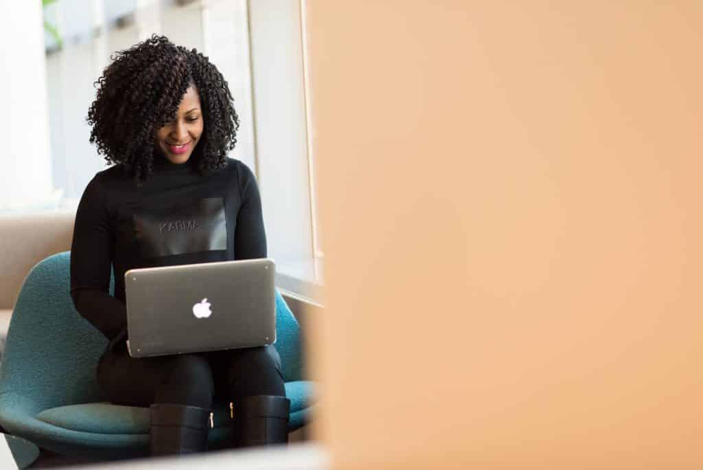 Mulher sentada em ambiente de escritório, usando o computador.
