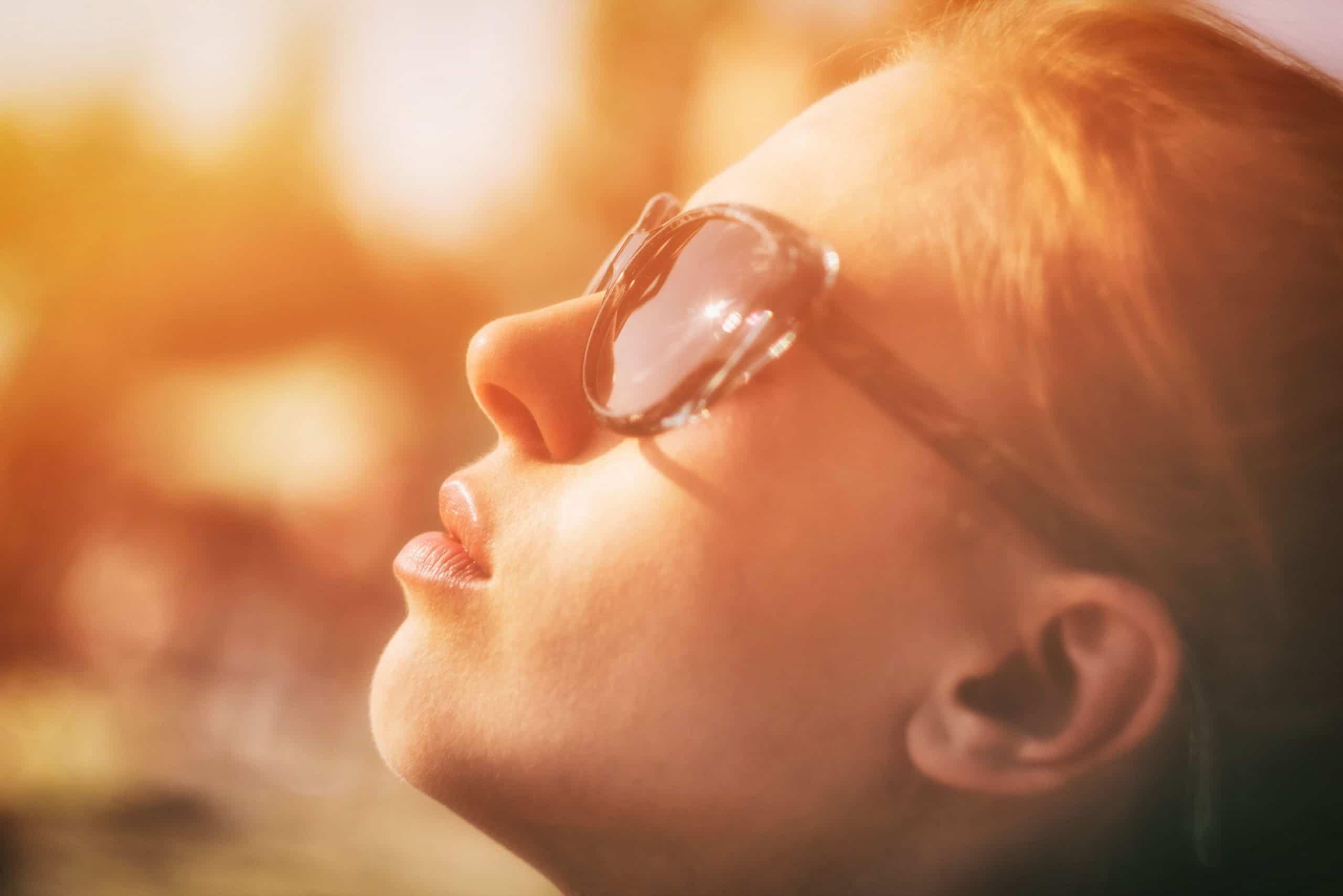 Mulher de perfil com óculos de sol com luz do sol refletindo