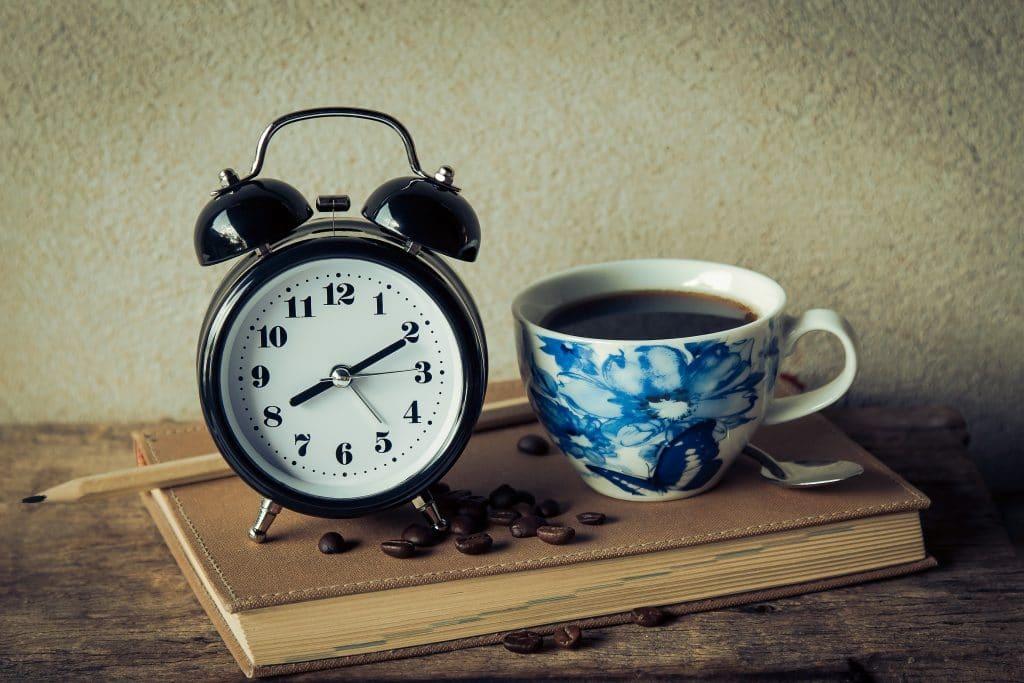 Relógio com despertador ao lado de uma xícara de café e grãos de café espalhados. Todos em cima de um livro fechado.