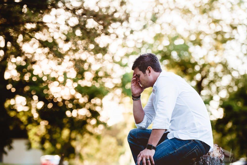 Homem sentado em um parque, com a mão sobre a testa, em sinal de cansaço.
