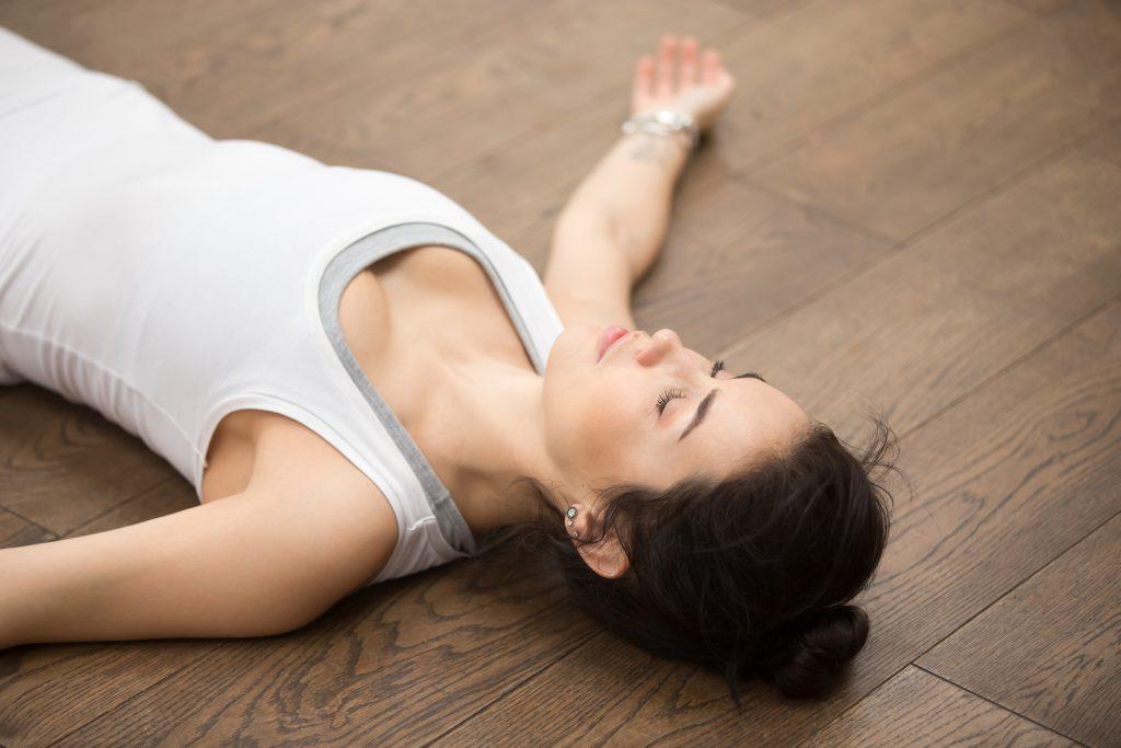 Mulher deitada no chão de braços abertos e olhos fechados