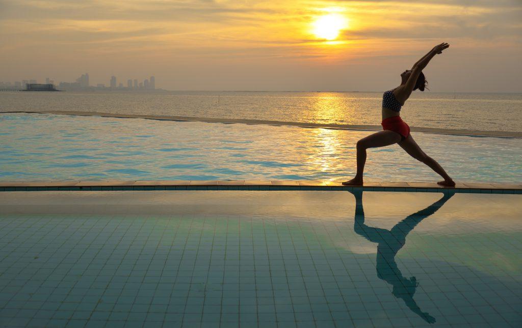 Mulher praticando Yoga em borda de piscina com mar e por do sol ao fundo