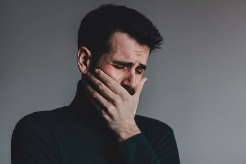 Homem com expressão de choro e a mão no rosto.