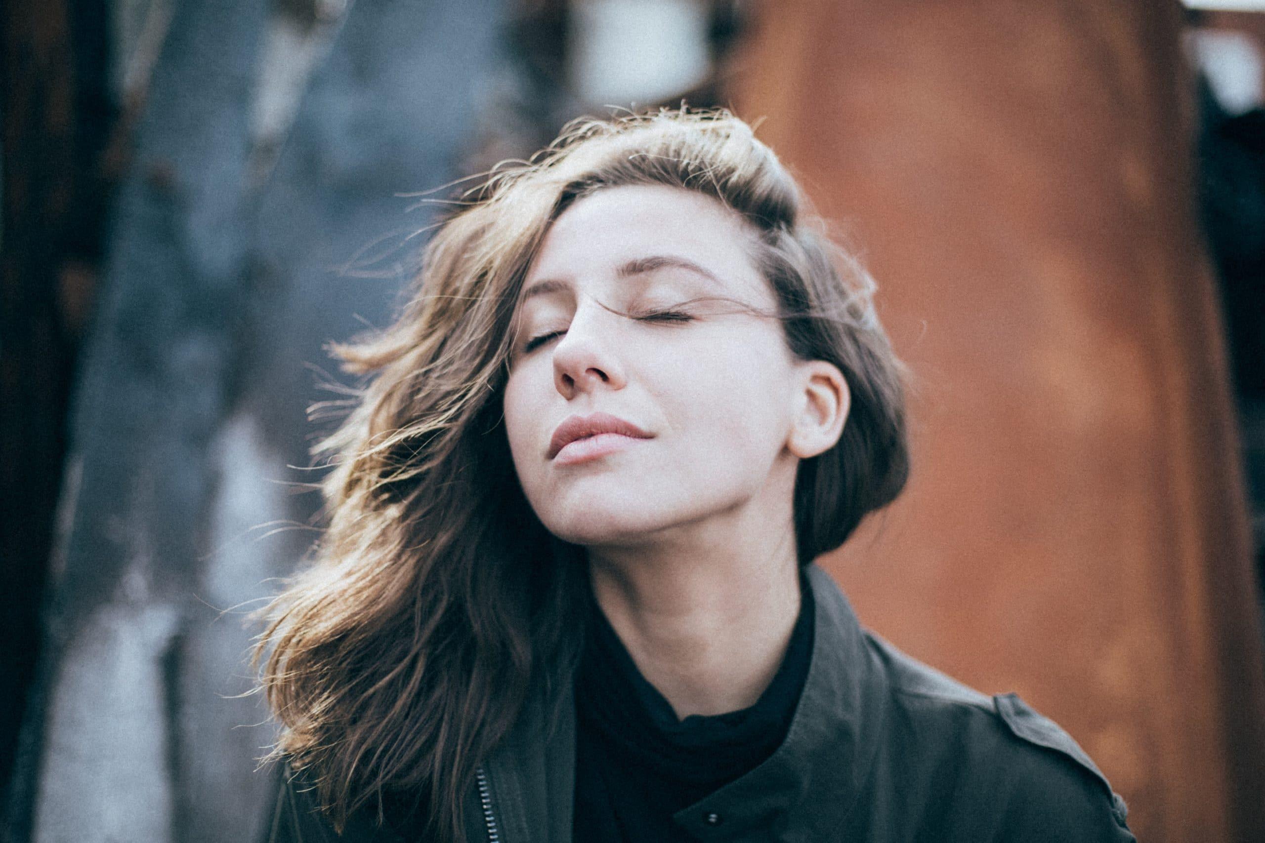 Mulher com cabelos ao vento de olhos fechados