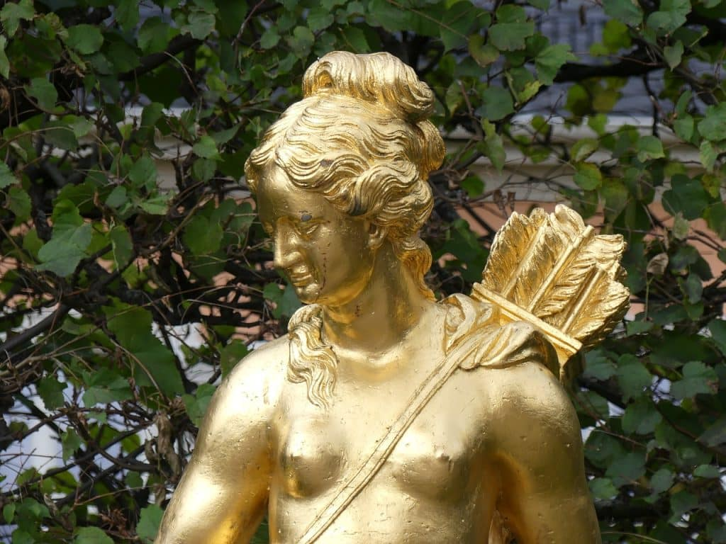 Estátua dourada de Ártemis, carregando flechas em uma bolsa em suas costas.
