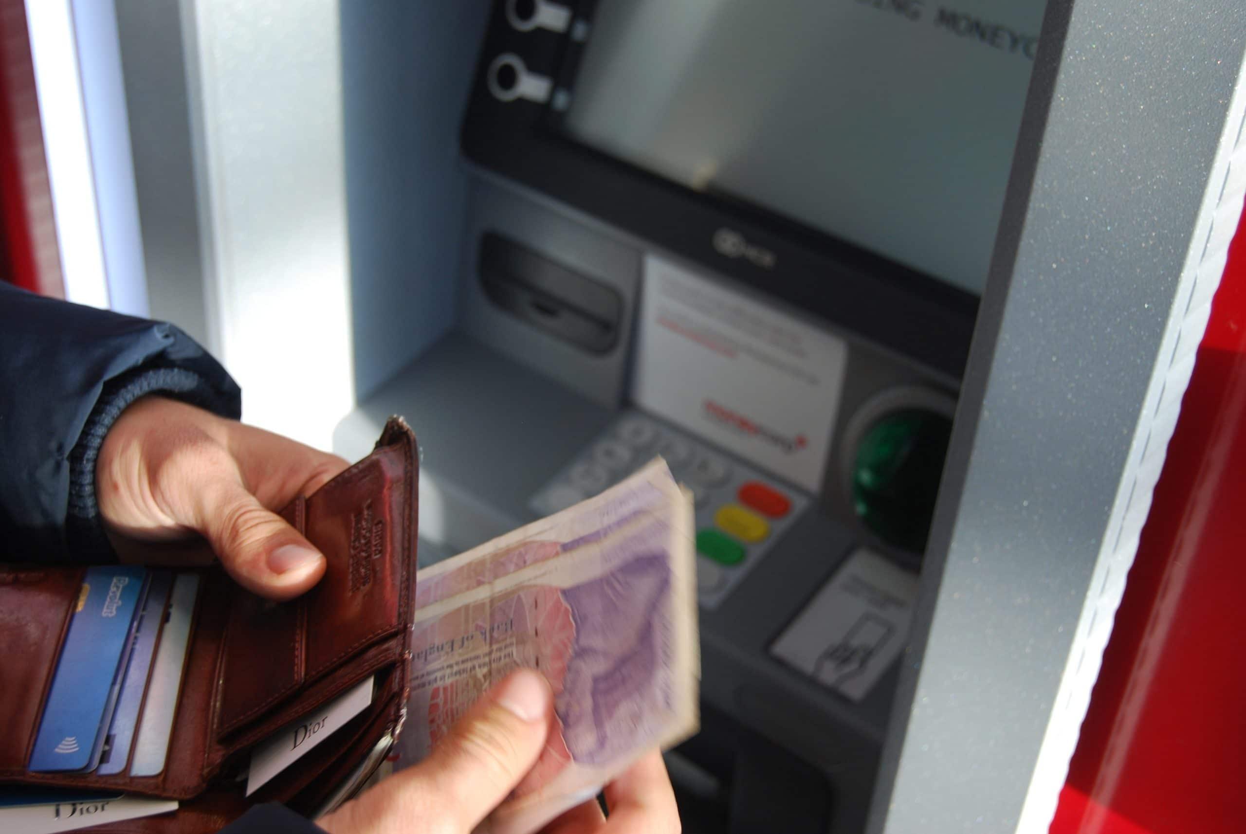 Mão sacando dinheiro em caixa eletrônico