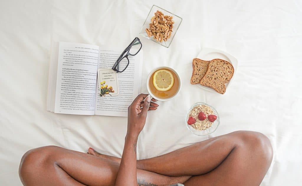 Mulher sentada de pernas cruzadas em uma cama. Em sua frente estão um livro aberto com um óculos em cima, um pote com nozes, um prato com duas fatias de pão e um copo com cereais e framboesas. Ela segura uma xícara com chá e uma rodela de limão com sua mão esquerda.