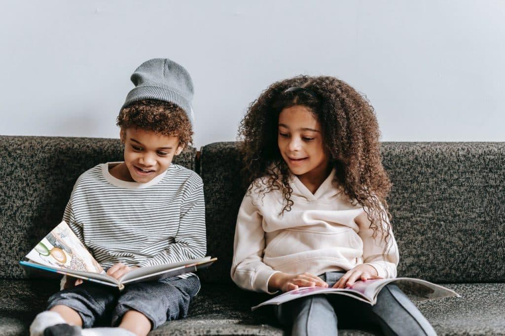 Duas crianças sentadas no sofá pintando um caderno.