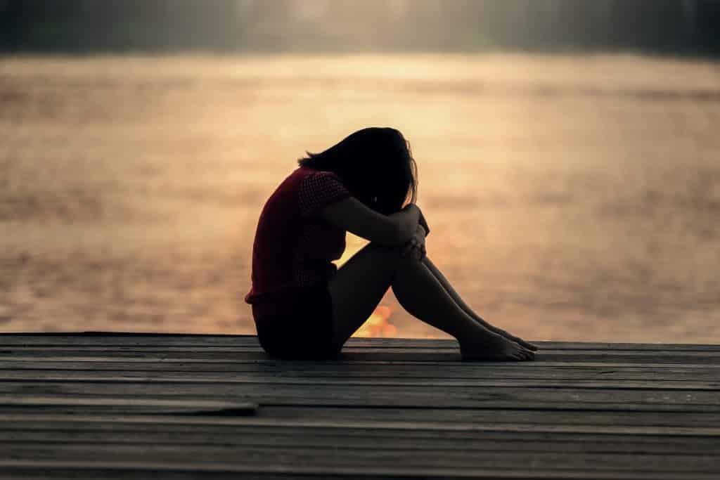 Mulher sentada na beira de um lago, de perfil, com a cabeça baixa e as mãos sobre os joelhos.