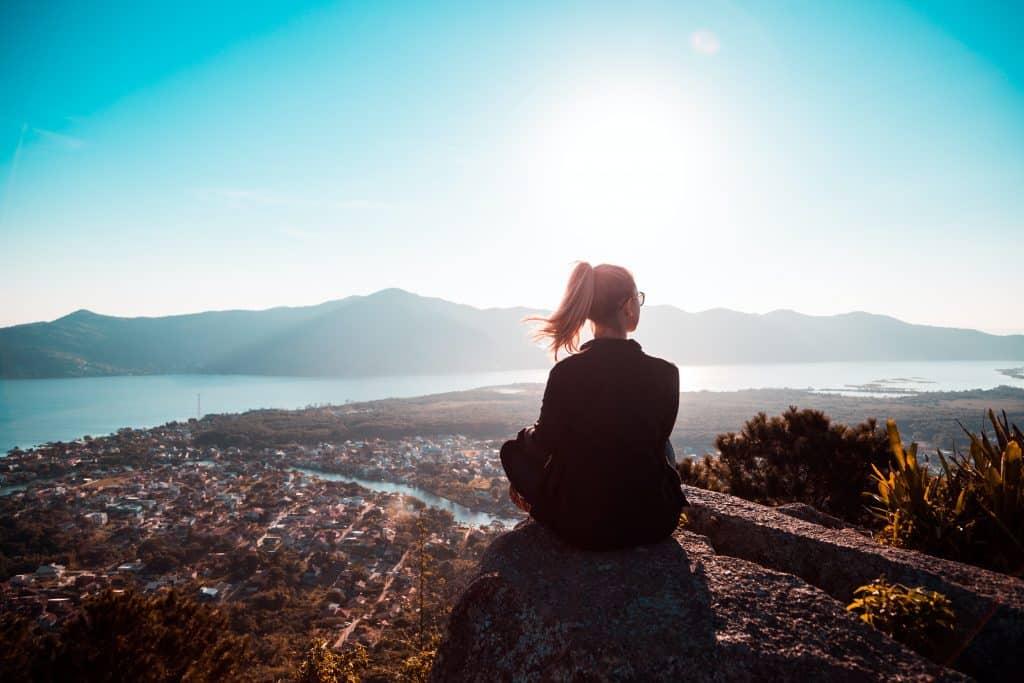 Mulher sentada de costas em paisagem natural.