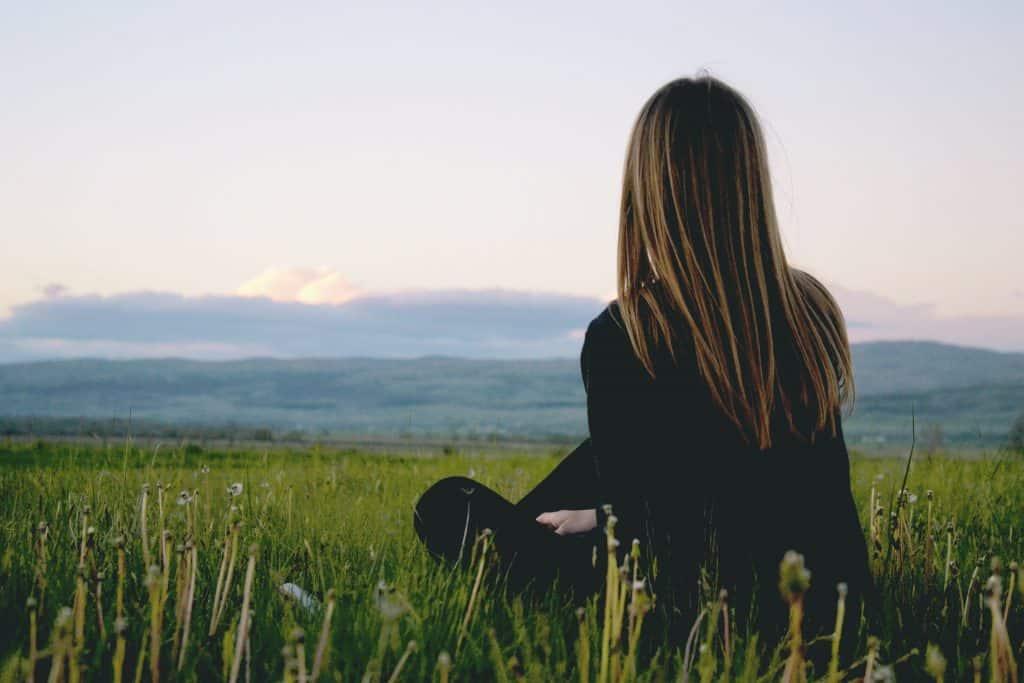 Mulher de cabelos lisos sentada de costas em um campo durante o dia, sozinha.