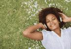 Mulher sorrindo deitada na grama ouvindo música