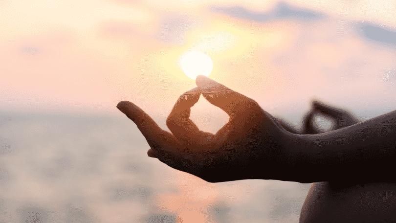 Mãos de uma pessoa meditando sob o pôr do sol