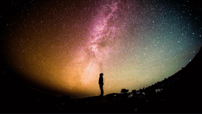 Silhueta de pessoa observando o céu estrelado
