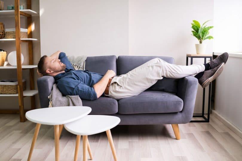 Homem deitado em sofá, com roupa social, cohilando.