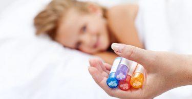 Menina sorrindo enquanto a mãe mostra vidrinhos com remédios de homeopatia.