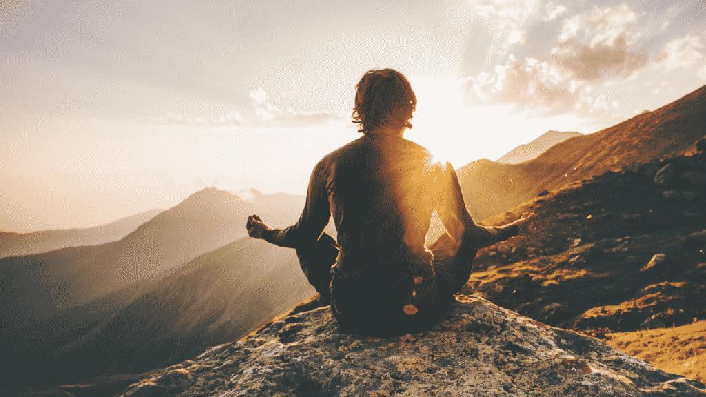Homem meditando no topo de uma montanha