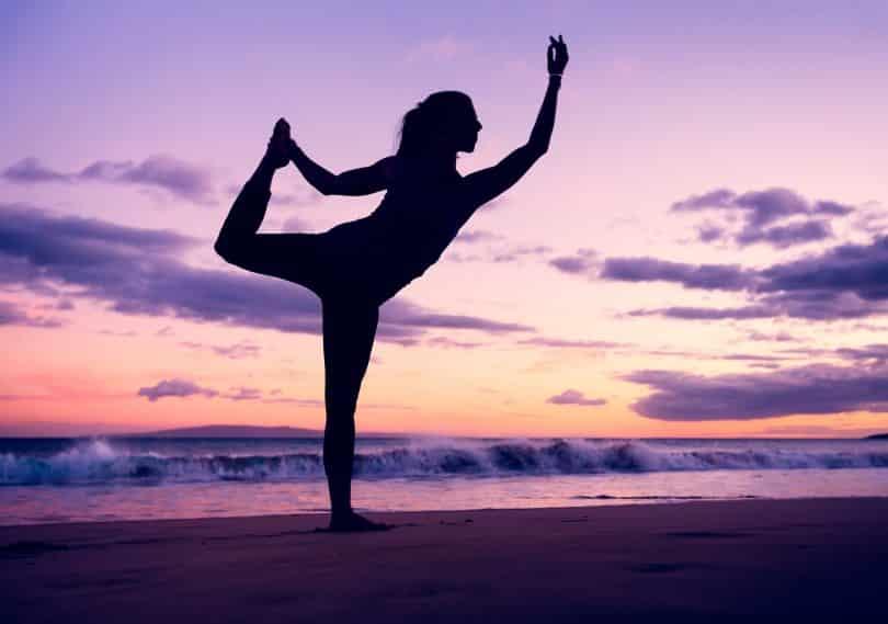 Mulher fazendo ioga na praia.