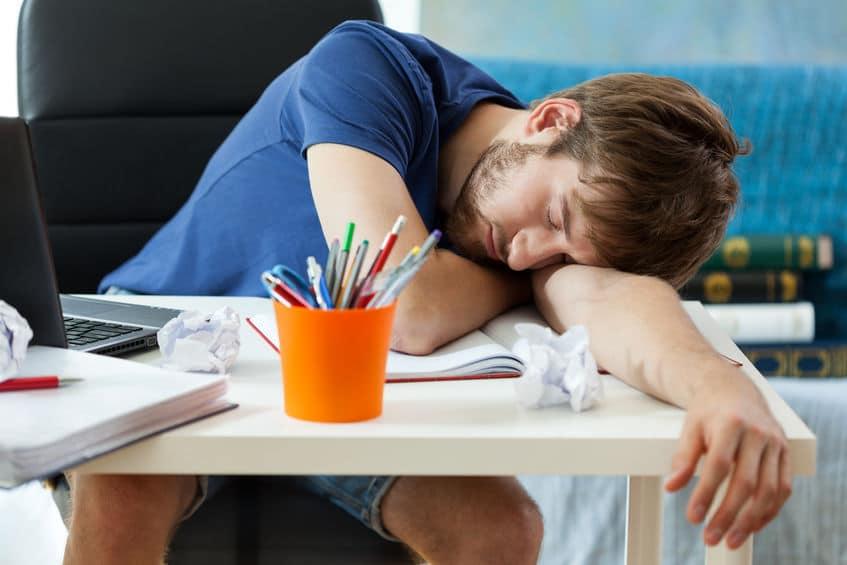 Homem com a cabeça apoiada em uma mesa, sobre seus braços e um caderno, dormindo.