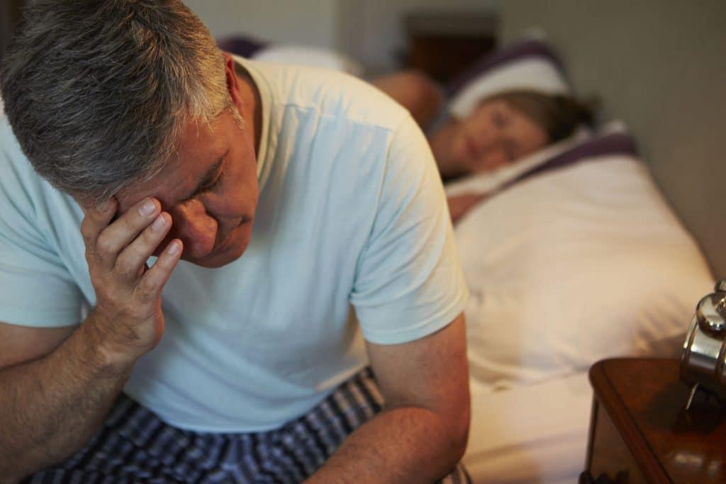 Homem acordado no meio da noite, com a mão sobre a testa, enquanto mulher dorme ao lado.