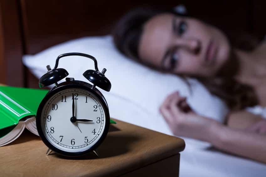 Mulher acordada à noite olhando para o relógio, que marca as 3 da manhã.