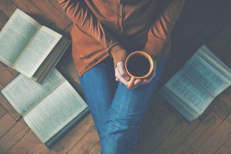 Mulher sentada no chão, com as pernas esticadas, segurando uma caneca com café. Ao seu redor, três livros estão abertos, também no chão.