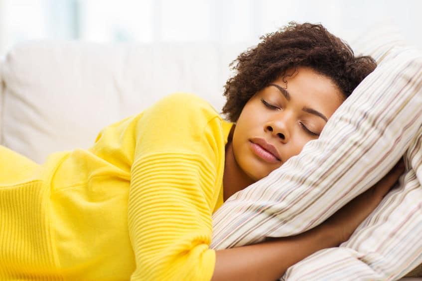 Mulher deitada dormindo, cochilando enquanto abraça uma almofada.