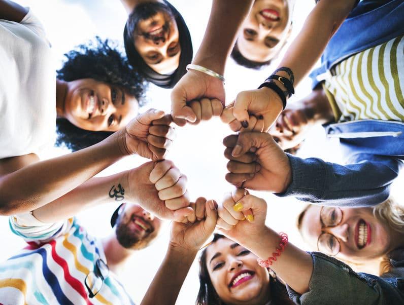 Grupo de amigos com as mãos unidas no centro