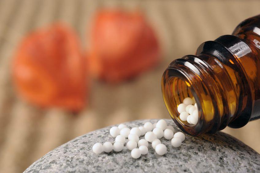 Vidro com remédio sendo colocado em uma pedra