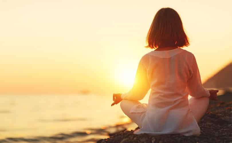 Garota sentada em posição de lótus em uma pedra ao pôr do sol.