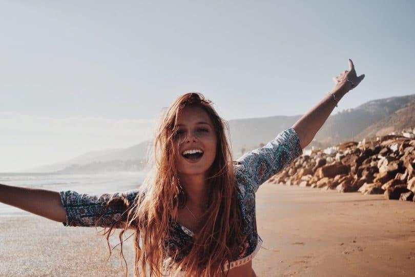 Mulher na praia com os braços abertos
