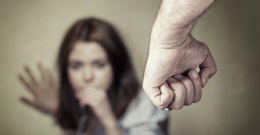 Mulher encostada em uma parede, com medo, ao fundo da imagem, e mais próximo da lente, em foco, um punho fechado.