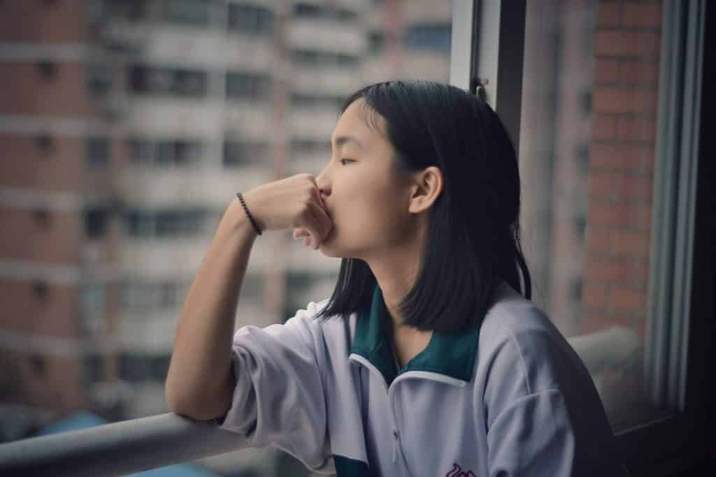 Mulher sentada na janela olhando para fora, com a mão sobre a boca.