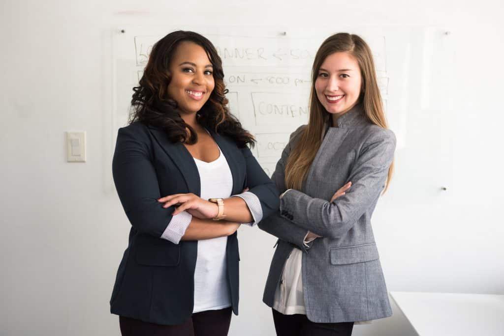 Duas mulheres em frente a uma lousa branca sorrindo e de braços cruzados