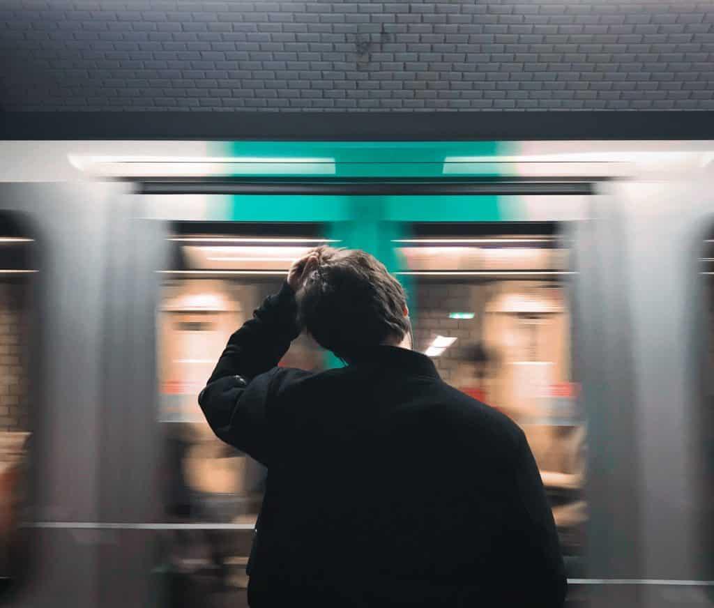 Pessoa de frente para um metrô em movimento, com a mão sobre a cabeça.