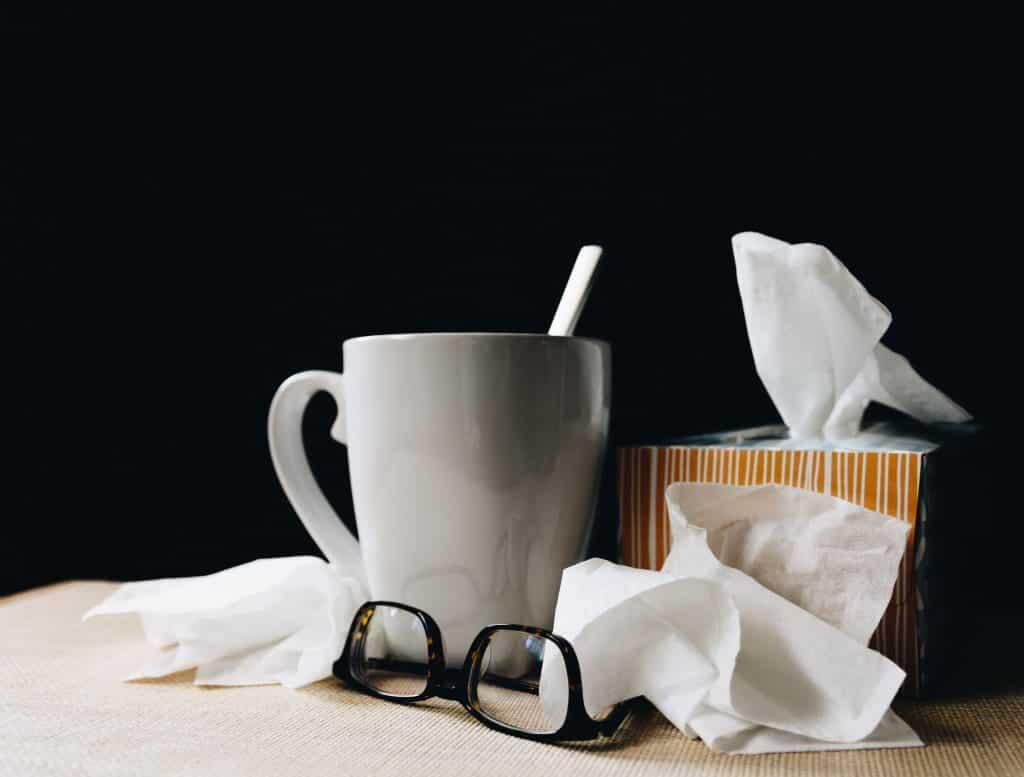 Caneca, lenços de papel e óculos sobre uma mesa.