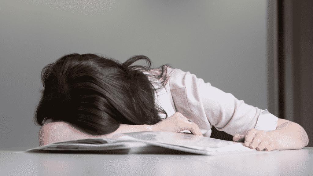 Mulher com a cabeça baixa sob a mesa