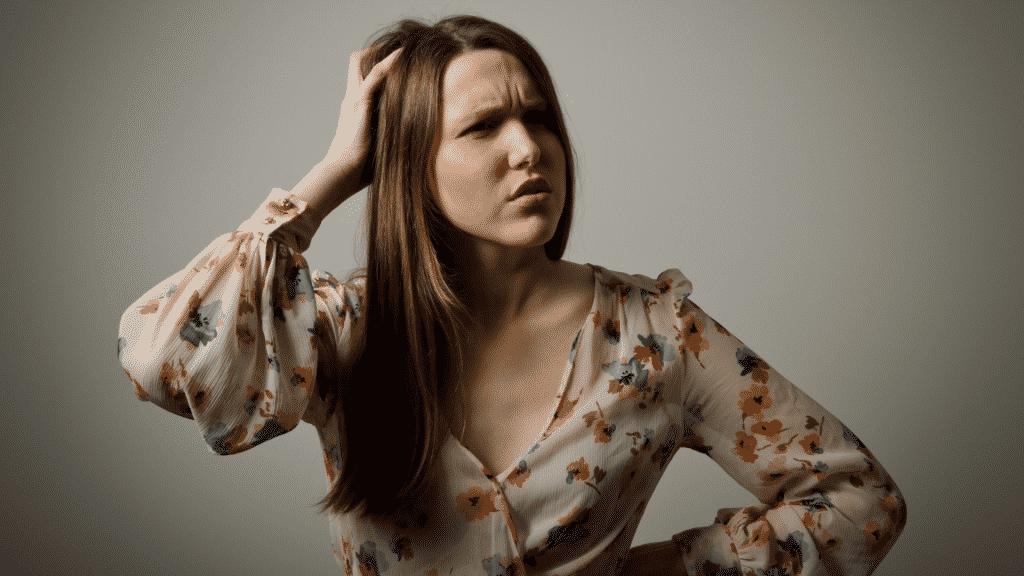 Mulher conçando a cabeça com expressão confusa que representa o esquecimento
