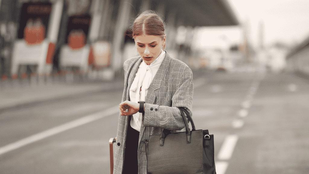 Mulher de terno olhando com expressão preocupada para o relógio