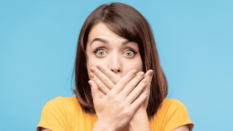 Mulher com expressão de surpresa e as mãos tampando a boca