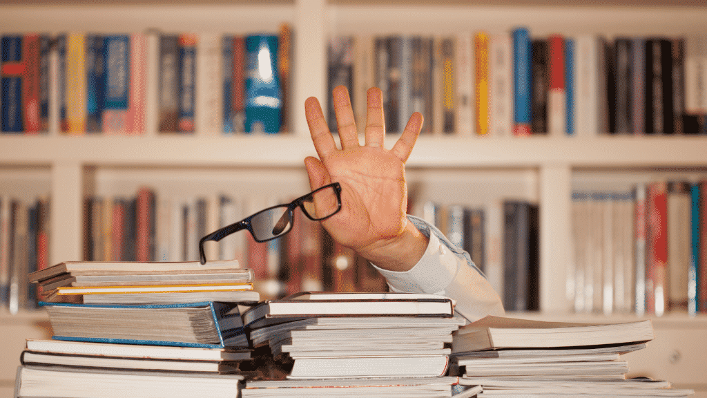 Mão segurando óculos atrás de uma montanha de livros
