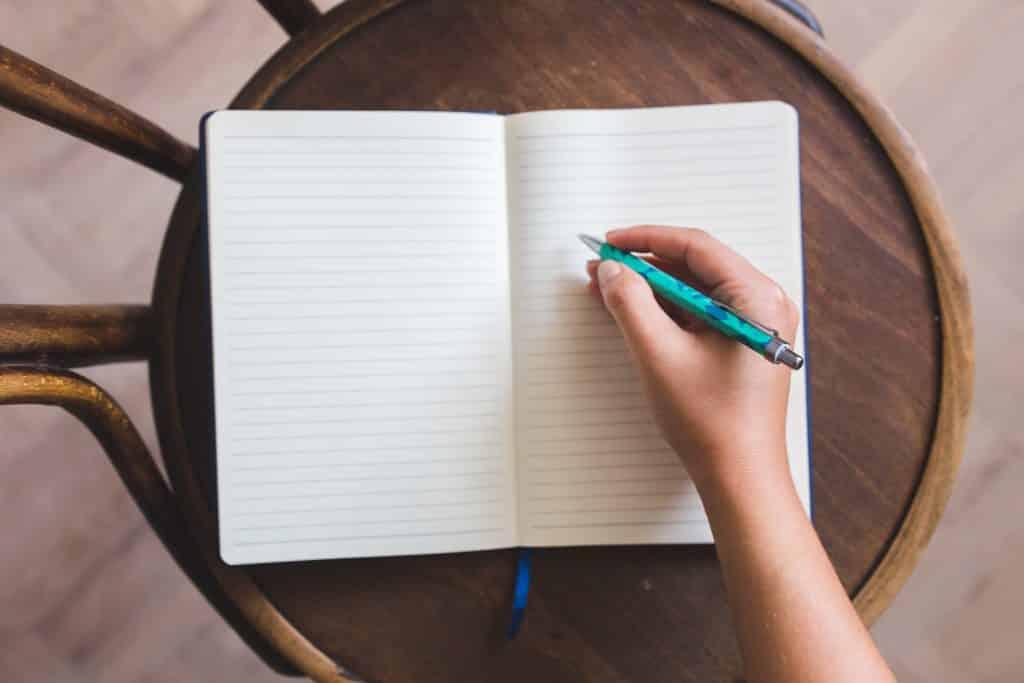Pessoa segurando uma caneta em frente a um caderno