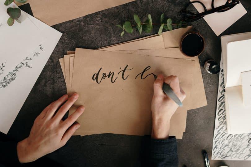 Pessoa escrevendo em uma folha ao lado de um potinho de tinta