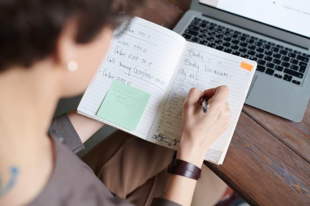 Pessoa escrevendo em uma agenda