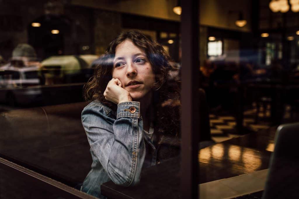 Mulher pensativa ao lado de uma janela
