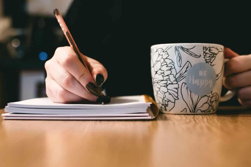 Mulher escrevendo em uma agenda enquanto segura uma caneca de café