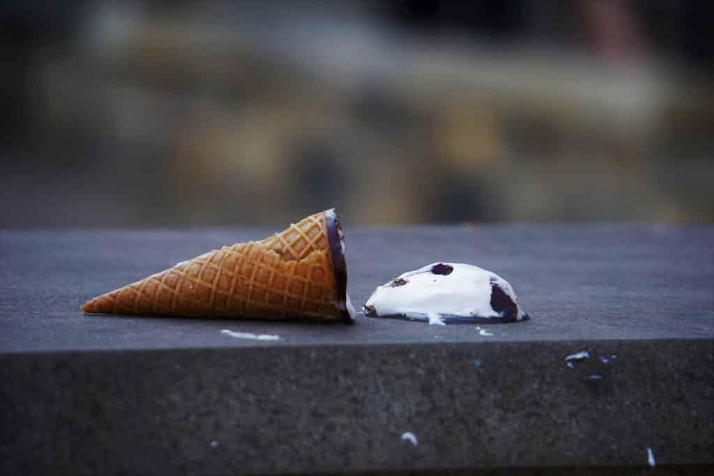 Casquinha de sorvete caída no chão.