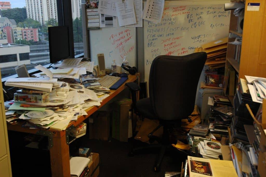 Cômodo de escritório repleto de papeis, CD's e materiais de escritório espalhados pelo chão.